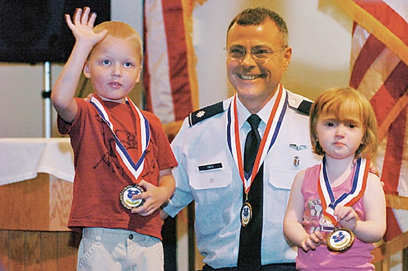 Wright-Patterson Air Force Base Young Heroes Association representative, Lt. Col. Rory Owen, presented Timothy Desmond Kingston and his sister Ada Lillian Kingston with Young Heroes Medals of Honor during a base ceremony on Oct. 4.  Owen was also presented an honorary Young Heroes Medal. (Skywrighter photo/Charles Caperton)
