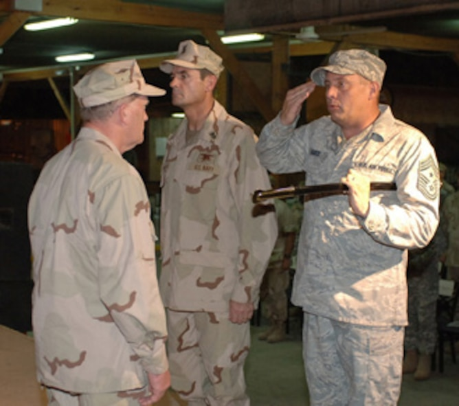 CAMP LEMONIER, Djibouti -- Chief Master Sgt. John R. Harris Jr., outgoing senior enlisted advisor for Combined Joint Task Force-Horn of Africa, salutes Rear Adm. James Hart, CJTF-HOA commander, during a Relief and Appointment Ceremony at Camp Lemonier's New Cantina Sept. 29. The ceremony marked the end to Harris' 13-month tour as HOA's senior enlisted leader and featured the passing of the sword, which represents the turnover of senior enlisted responsibilities from Harris to Navy Command Master Chief Roy Maddocks. U.S. Navy photo by Mass Communication Specialist 1st Class Mary Popejoy (RELEASED)