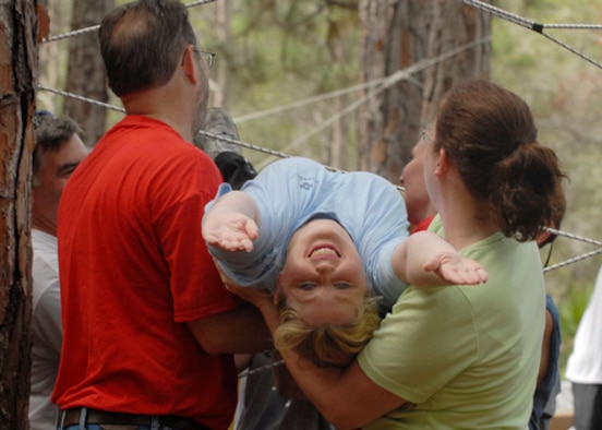"Laura Ryan is carefully carried through a small opening in the ""spider web"" by teamates Tim Putnam and Katie Cherry during a teambuilding exercise held at Tyndall's Ropes Course Oct. 5 .  The object of the exercise was to get each person in the team through the web without touching the ropes and only using each opening once. Bonita Bay personnel take reservations and teach the course like the one these participants from Bay County Chamber of Commerce's Leadership Bay attended."