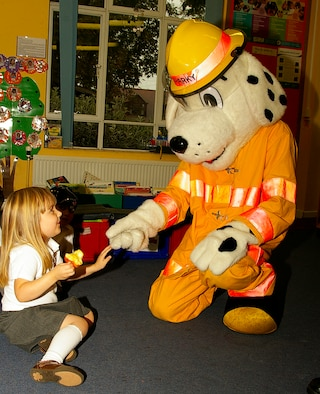Megan McCrea, 4, greets Sparky the Fire Dog during a visit to France Class at Beck Row Primary School Oct. 9, as part of Fire Prevention Week. (U.S. Air Force photo by Karen Abeyasekere)