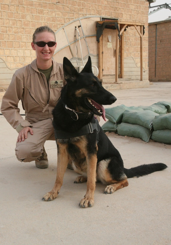 Sgt. Jaimi Diaz, a dog handler with Task Force Military Police, poses for a photograph with her dog, Darrah. Diaz is currently the kennel master in Al Qaim, Iraq, and is running patrols with 1st Battalion, 4th Marine Regiment.