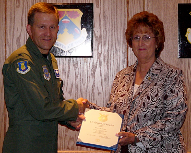 Col. John Zazworsky, acting 22nd Air Refueling Wing commander, presents Mary Eary, 22nd Mission Support Group executive secretary with a certificate of service and pin for her 50 years of service as of Sept 10 working as a civil service member. (curtesy photo)