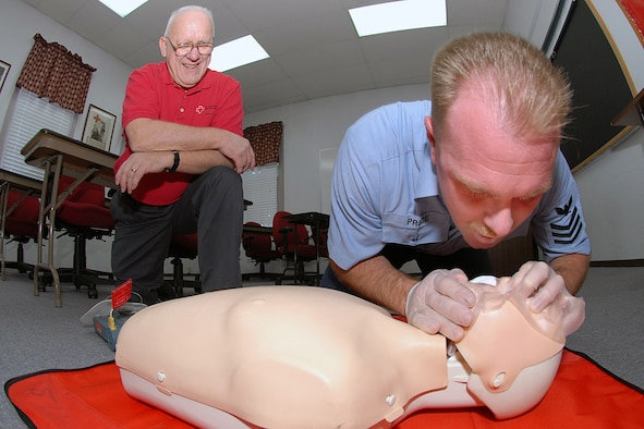 Petty Officer 1st Class William Price, U.S. Transportaion Command aviation structural mechanic and Red Cross Blood Drive chairman, conducts a Cardiopulmonary Resuscitation class as Paul McLaughlin, Red Cross Health and Safety chairman, observes and provides feedback.