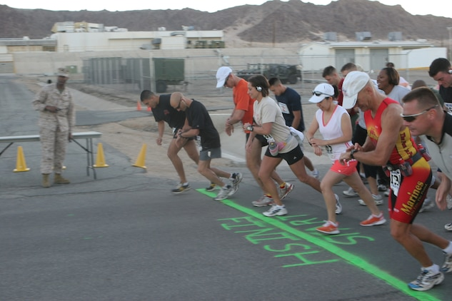 Runners start their stopwatches as they take off from the starting line in front of Combat Center building 1831 and kick off the 4th Marine Corps Communication-Electronics School Fun Run Oct. 19.