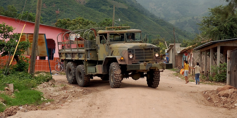 SOTO CANO AIR BASE, Honduras – An Army two-and-a-half-ton troop transport truck rolls through the village of Lejamani as part of a convoy exercise Oct. 19.  The purpose of the training was to keep the vehicles in operation and identify any issues with them so they could be fixed.  (U.S. Air Force photo by Staff Sgt. Austin M. May)