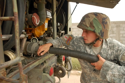 SOTO CANO AIR BASE, Honduras – Army Sgt. Andrea Dickey hooks up a fuel hose to a tanker truck during a simulated Refuel on the Move, or ROM, during a convoy exercise near the village of Lejamani Oct. 19.  The purpose of the training was to keep the vehicles in operation and identify any issues with them so they could be fixed.  (U.S. Air Force photo by Staff Sgt. Austin M. May)