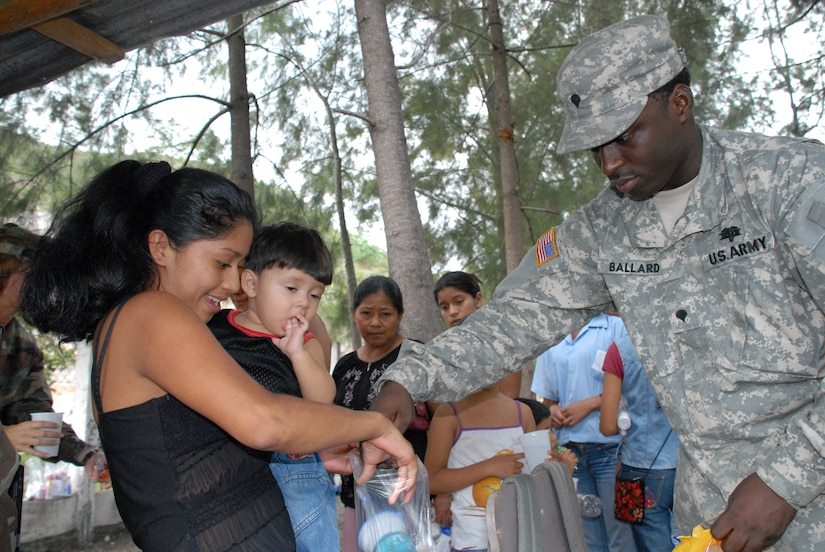 CUESTA DE LA VIRGEN, Honduras -- Army Spec. Roderick Ballard, a medical logistics technician, hands out candy to local Honduran children Oct. 19 during a Medical Readiness Training Exercise.  This MEDRETE educated 785 Hondurans on preventive medicine issues such as hand washing, food preparation and personal hygiene.  Of those 785, doctors examined 352 patients and the dentist treated 139 patients. (U.S. Air Force photo/Tech. Sgt. Sonny Cohrs)