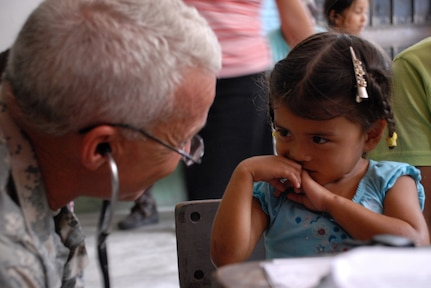 CUESTA DE LA VIRGEN, Honduras -- Army Lt. Col. (Dr.) Michael Hoilien, assigned to the Medical Element at Soto Cano Air Base, examines a Honduran child during a Medical Readiness Training Exercise here Oct. 19.  This MEDRETE educated 785 Hondurans on preventive medicine issues such as hand washing, food preparation and personal hygiene.  Of those 785, doctors examined 352 patients and the dentist treated 139 patients.  (U.S. Air Force photo/1st Lt. Erika Yepsen)