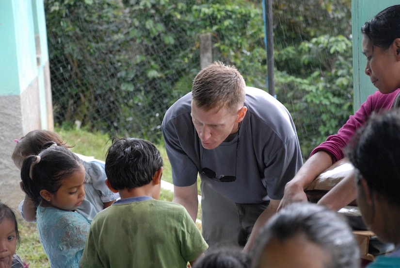 ALDEA BELLA VISTA, Honduras -- U.S. Air Force Maj. Jason Clark hands food to children in Bella Vista Oct. 20.  Major Clark was one of approximately 50 U.S. military members who hiked up Comayagua Mountain to bring 450 pounds of food to the residents in remote Bella Vista.  The hike was organized by the JTF-Bravo chaplain to support local Hondurans.  Approximately 50 military members participated in the hike which was the second in a series of five planned to date. (U.S. Air Force photo/1st Lt. Erika Yepsen)