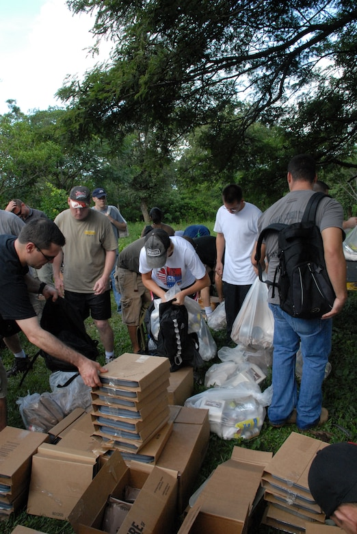 ALDEA BELLA VISTA, Honduras -- U.S. military personnel load their packs and backpacks with food Oct. 20 to deliver to people in the village of Bella Vista.  The hike was organized by the JTF-Bravo chaplain to support local Hondurans.  Approximately 50 military members participated in the hike which was the second in a series of five planned to date. (U.S. Air Force photo/1st Lt. Erika Yepsen)