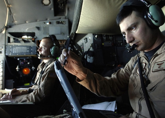 AFGHANISTAN -- U.S. Air Force Maj. Jaska Cason, C-130 Hercules aircraft mission commander, calculates, coordinates and prepares his crew before dropping 30,000 warning leaflets over the southeastern mountains of Afghanistan.  The leaflets were used to communicate with Taliban extremists, warning them not to interfere with Coalition activities.  The leaflet airdrop mission is helping to create an environment that will enable the government of Afghanistan to help improve security and the Afghan people's quality of life.  (U.S. Air Force photo by Tech. Sgt. Cecilio Ricardo, Released)