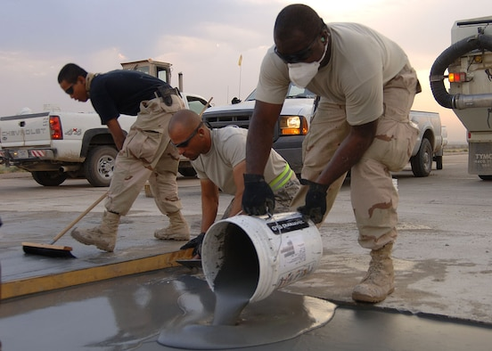 "SATHER AIR BASE, Iraq -- Tech. Sgt. Freddie Garrette pours freshly mixed concrete into a 100 square foot spall repair area Oct. 6 while Tech. Sgt. Jeff Jones, center, smoothes the edges and Senior Airman Wilson Quinante brushes the surface of a smoothed section to give it an anti-skid surface. The 447th Expeditionary Civil Engineer Squadron Heavy Equipment Operations ""Dirt Boys"" repair damaged surface areas on the airfield here each Saturday morning. The team gets an early start, often working before sunrise, to beat the daytime high temperatures, which helps ensure a proper mixture cure time and a stronger slab. The team must also work quickly to limit the amount of time airfield operations are affected while repairs are done. Sather AB is the busiest airfield in Iraq, averaging 4,000 transient aircraft activities each month. Sergeant Garrette is deployed from the Tennessee Air National Guard. Sergeant Jones is deployed from Elmendorf Air Force Base, Alaska.  Airman Quinante is deployed from Eglin Air Force Base, Fla. (Staff Sgt. Jennifer Lindsey)"