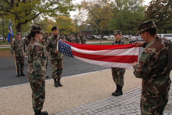 From left, Airman 1st Class Melissa Nguyen, Capt. Michael Nedrow, 1st Lt. Christie Jones and Senior Airman Nathan Lopez, all 554th Electronic Systems Wing personnel, fold the U.S. flag during a Retreat Ceremony held outside of building 1606 Oct. 18. (U.S. Air Force photo by Dennis Lewis.)