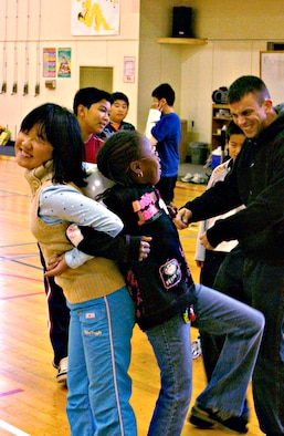 MISAWA AIR BASE, Japan -- Mao Kashiwazaki and Faith Moss play a game where the object is to pop a balloon between their backs at Sollars Elementary School, Oct. 20, 2007. Mao is a student at Kinoshita Elementary School in Oirase Town participating in a cultural exchange program here on Misawa where Faith attends school. (U.S. Air Force photo by Airman 1st Class Eric Harris)(RELEASED)