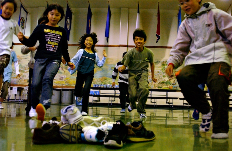 MISAWA AIR BASE, Japan -- Japanese elementary school students run to pickup a shoe as part of a game to meet and interact with American students at Sollars Elementary School, Oct. 20, 2007.  The Japanese children came from three elementary schools in Oirase Town as part of a cultural exchange program that has been running for 15 years. (U.S. Air Force photo by Airman 1st Class Eric Harris)(RELEASED)