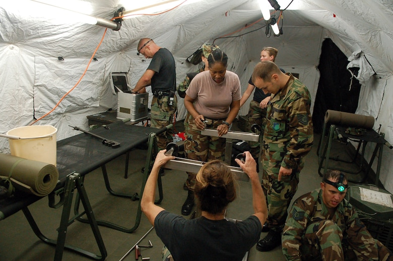 Members of the Joint Task Force-Bravo Medical Element work together to set up medical equipment inside a Mobile Surgical Team tent in an empty field here Oct. 18.  The team set up the mobile operating room at night to practice setting up in limited visibility.  (U.S. Air Force photo by Staff Sgt. Austin May)