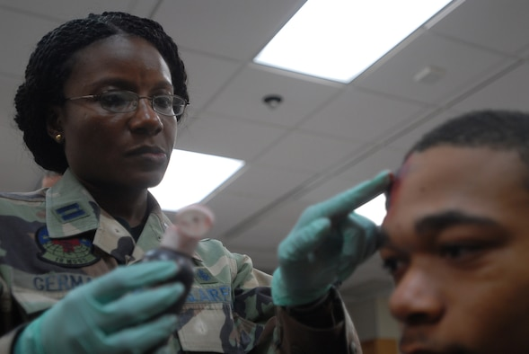 "Capt. Mickaelle Germain, 18th Medical Operations Squadron, applies moulage to the head of Airman Basic Lemar Mayberry, 18th Component Maintence Squadron, to simulate a wound during an exercise scenario at Kadena Air Base, Japan, Oct. 24, 2007.  Moulaged ""victims"" provide more realism to exercise scenarios. The Airmen are supporting training missions based on real-world scenarios as part of Local Operational Readiness Exercise Beverly High 08-1. (U.S. Air Force photo/Senior Airman Darnell T. Cannady)"