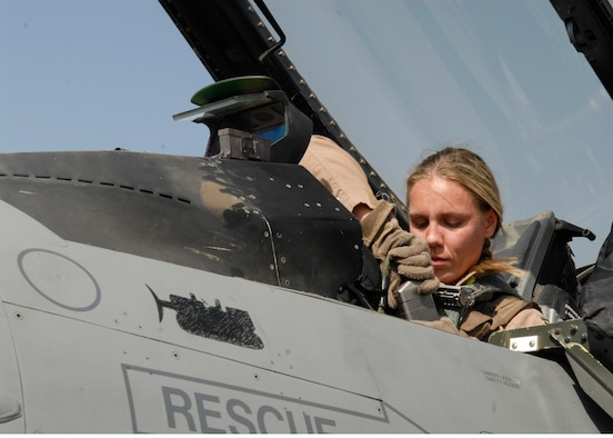 BALAD AIR BASE, Iraq -- Capt. Caroline Jensen, 4th Expeditionary Fighter Squadron, connects the communications receiver to her helmet ensuring she is contact with personnel on the ground. All aircraft equipment is checked prior to a flight to ensure it is functioning properly. Captain Jensen is currently deployed from Hill Air Force Base, Utah. (U.S. Air Force photo/Staff Sgt. Joshua Garcia)