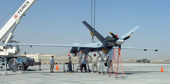 A team of testers lifts the MQ-9 Reaper Unmanned Aerial Vehicle for a landing gear operational check. The Air Force Operational Test and Evaluation Center Detachment 5 and the 31st Test and Evaluation Squadron recently tested the Reaper system's ability to deploy to a forward operating location in support of mission tasking. The team performed the testing at Kandahar Air Base, Afghanistan, from Sept. 4 through 25. (Courtesy photo)