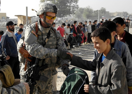 Master Sgt. William Whitt passes out soccer balls and gear to local children from the Kabul Youth Soccer League Oct. 22 outside the gate at Kabul International Airport, Afghanistan. The equipment was donated by businessmen and supporters from Tennessee, Georgia and California. Sergeant Whitt's wife, Lea-Ellen Whitt, was instrumental in the effort in Tennessee. (U.S. Air Force photo/Staff Sgt. Brian Ferguson)