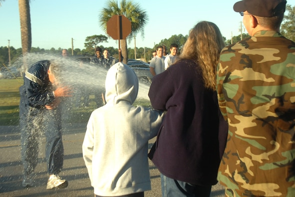 EGLIN AIR FORCE BASE, Fla. -- Col. Dean Clemons, 96th Air Base Wing commander, gets hosed down by his wife, Lisette and son Isaac after a wing run.  Colonel Clemons is departing the wing for a year-long deployment in Iraq. (U.S. Air Force photo by Staff Sgt. Mike Meares)