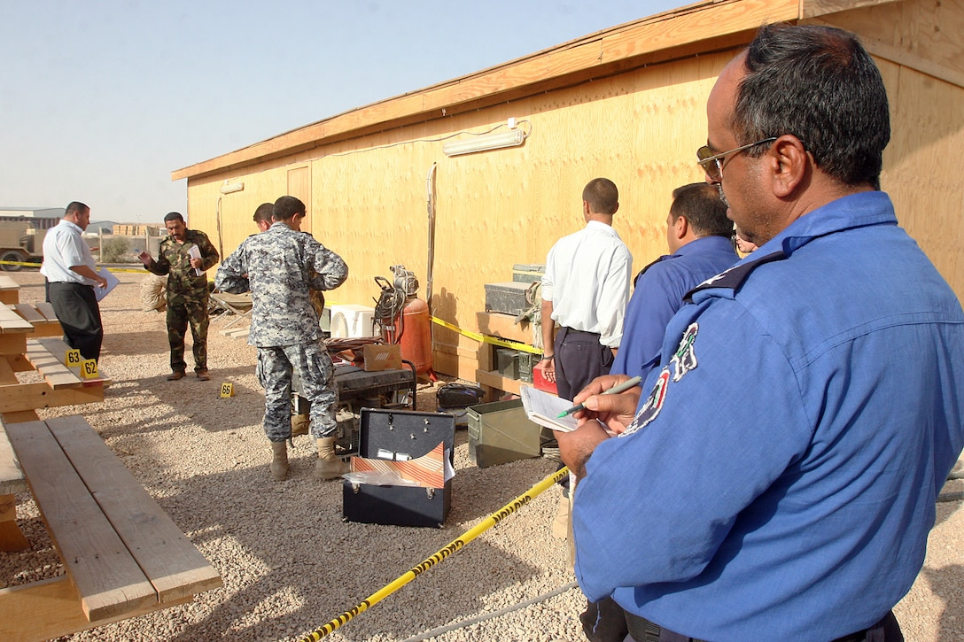 AL ASAD AIR BASE, Iraq, – An Iraqi police officer instructing the Basic Criminal Investigation Course here evaluates students participating in a final exercise, where they combine what they learned during the course to a fake crime scene. Leading up to the final exercise, the students learned about democratic policing and ethics, both of which focus on teaching officers they are committed to serving the public, and they have moral responsibilities to the community. Official Marine Corps Photo By Cpl. Ryan C. Heiser.