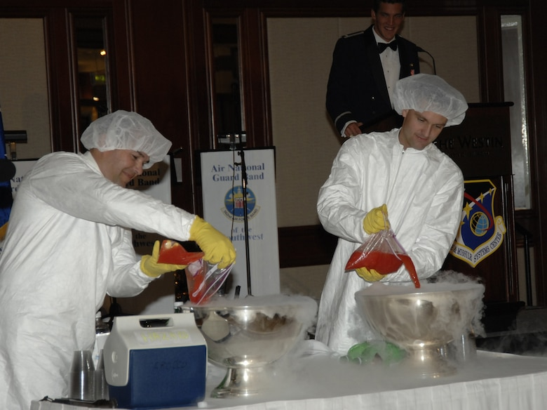 """Major Kevin Crocco and Major Mark Hadley, both from the MILSATCOM Wing, donned clean room suits as they charged the """"grog"""" with a secret ingredient from the Third Floor of Bldg. 271.  Several rules were laid out in the program and announced at the beginning of the evening. The penalty for breaking any of the rules, if caught, was a trip to the Grog Bowl. Approximately 600 people gathered at the Westin Hotel Ballroom in Long Beach Oct. 20 for this year's Space and Missile Systems Center's Dining Out. (Photo by Lou Hernandez)"""