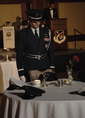 Capt Jim Manna, a member of the Los Angeles AFB Honor Guard from the SBIRS Wing, honors missing comrades in arms at this year's Space and Missile Systems Center's Dining Out.  The empty table represents Americans still missing from each of the five Armed Services.  This honors ceremony symbolizes that they are with us, here in spirit. (Photo by Lou Hernandez)