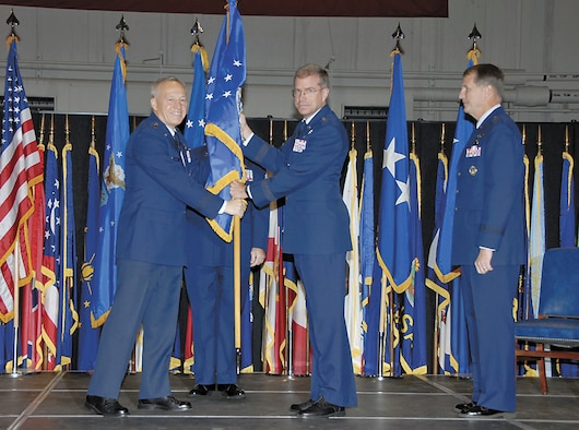 Gen. Bruce Carlson passes the AFRL flag to Maj. Gen. Curtis Bedke as he assumes command of the Air Force Research Laboratory.  Outgoing commander Maj. Gen. Ted Bowlds looks on. Bowlds, a Lt. Gen. select, will next command Electronic Systems Center at Hanscom Air Force Base, Mass. (Christy Webb/Skywrighter photo)