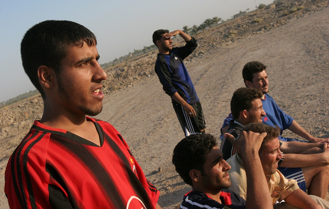An Iraqi man rests as his comrades play in a competitive soccer game as part of the Habbaniyah areas new soccer league, which was formed here recently.  The players in the league come from the surrounding area where they all contribute to their community.  Their occupations range from local Iraqi Security Forces personnel to local construction workers or farmers.  Iraq?s love of football is no longer shared just over a televised event and some hot chai tea, it is now played in the open and for fun, said Kemal Musceff, a 26 year-old center fielder for the Jimaylan football team.