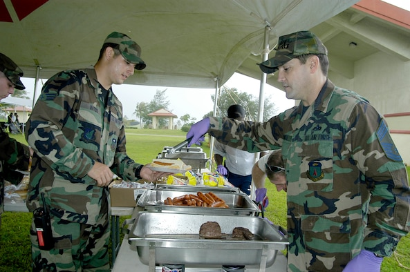 Chief Master Sgt. James Cornell, 36th Maintenance Group, serves a hot dog to Senior Airman Christopher Bates, 36th Logistic Readiness Squadron, during the annual Andersen Junior Enlisted Appreciation Day Oct 26. (U. S. Air Force photo/ Master Sgt. Lisa M. Zunzanyika)