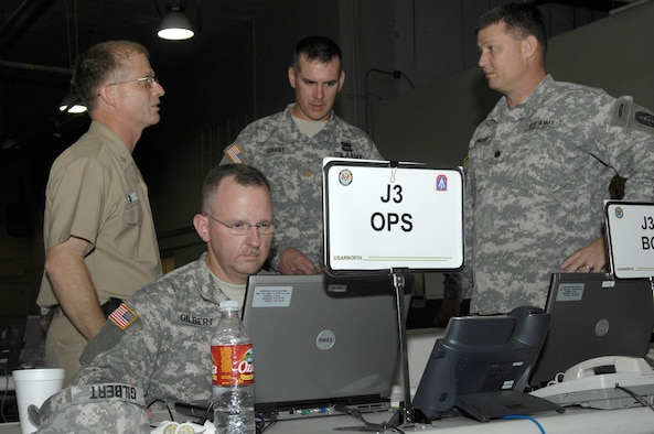 Capt. Eugene Dawydiak, left, Maj Andy Gilbert, Maj. Eric Grant and Lt. Col James Skidmore monitor and coordinate joint military efforts as part of a federal support package used to assist federal, state and local agencies responding to the California wildfires at March Air Force Base in Riverside, Calif., Oct. 25, 2007.  (U. S. Air Force photo by Senior Airman Daniel St. Pierre)