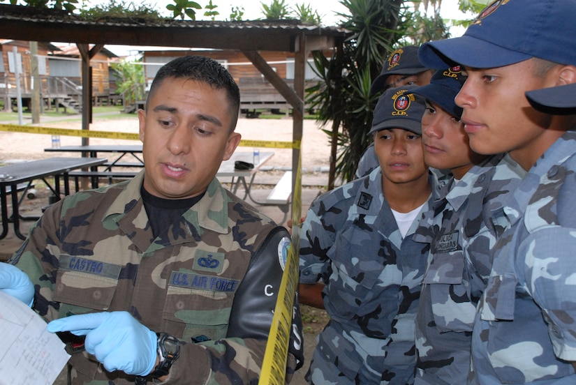 SOTO CANO AIR BASE, Honduras -- Air Force Staff Sgt. Edgar Castro, Joint Security Forces, explains crime scene processing paperwork to students from the La Paz Police Academy during a training course here.  The crime scene processing class is one in a series of classes taught this year, with other lessons involving handcuff procedures, high-risk traffic stops and riot control.  (U.S. Air Force photo/Tech. Sgt. Sonny Cohrs)