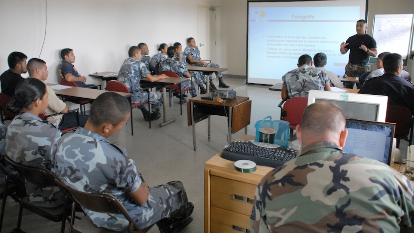SOTO CANO AIR BASE, Honduras -- Air Force Staff Sgt. Edgar Castro, Joint Security Forces, reviews crime scene procedures with police from nearby Comayagua and La Paz police divisions, as well as cadets from the La Paz Police Academy.  The course is one in a series of classes taught this year, with other lessons involving handcuff procedures, high-risk traffic stops and riot control.  (U.S. Air Force photo/Tech. Sgt. Sonny Cohrs)