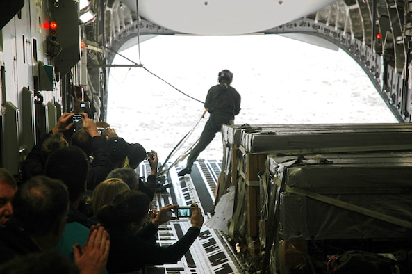 Civilian employers watch Tech. Sgt. Rob Withrow, a loadmaster in the 313th Airlift Squadron, after the  C-17 released a container delivery bundle over a drop zone Oct. 20.  The employers spent Oct. 20 learning about the mission and duties of their employees who also serve in the Air Force Reserve with the 446th Airlift Wing, McChord Air Force Base, Wash.  (U.S. Air Force photo/Senior Airman Grant Saylor)