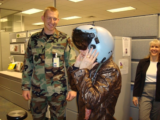 Ms. Peyton tries on the Joint Helmet Mounted Cueing System while 1st Lt. Cary Wilson looks on. (Air Force photo by Capt. Greg Justice)