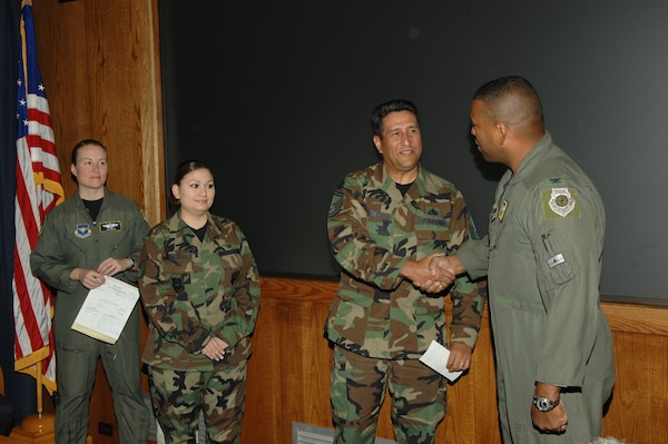 (Left Center) Senior Master Sgt. Ray Perez, Randolph Hispanic Council president, presents a $1,500 check to Col. Richard Clark, 12th Flying Training Wing commander, to be donated to the Boysville Childrens Home thorugh the Combined Federal Campaign on behalf of the wing and the Hispanic Council while (Far Left) Maj. Joey Dible, Randolph CFC project officer, and Staff Sgt. Miriam Saiz, Hispanic Council secretary, look on.