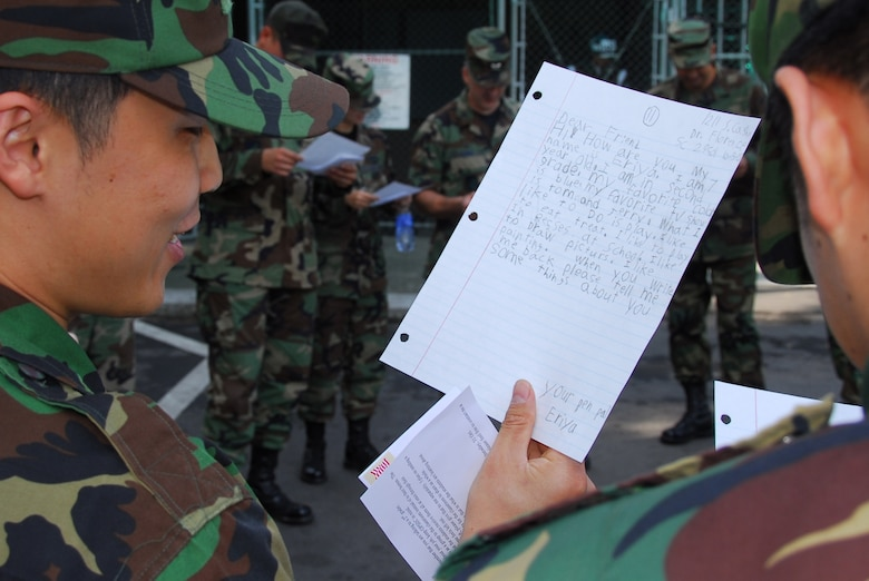 OSAN AIR BASE, Republic of Korea --  Airmen with the Republic of Korea Air Force read a letter from a 2nd grade students at Delmae Heights Elementary School on Oct. 26. Tech. Sgt. C.J. Baker, 607th Air Intelligence Squadron, and Veronica Flowers, a teacher at Delmae Heights in Florence, S.C., started a program in which Osan Airmen will be pen pals for one year with her 20 students. (U.S. Air Force photo by Staff Sgt. Ronnie Hill)