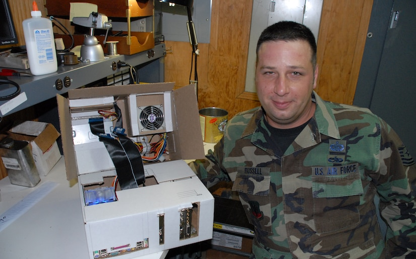 """SOTO CANO AIR BASE, Honduras -- Tech. Sgt. Robert Russell, Armed Forces Network Honduras chief engineer, shows off his """"Frankenstein computer"""" he built from spare parts and a shipping box. The computer took about two weeks to build, since he had to wait on the glue to dry and cure after each computer component was added.  (U.S. Air Force photo/Tech. Sgt. Sonny Cohrs)"""