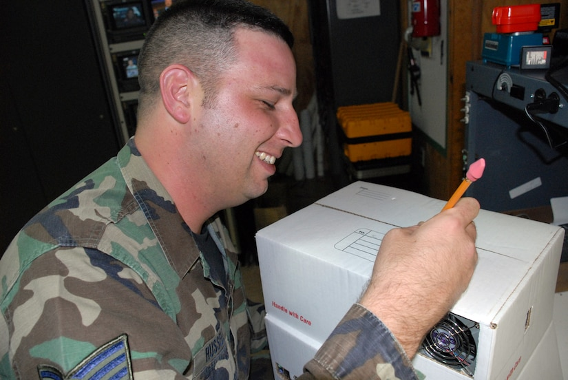"""SOTO CANO AIR BASE, Honduras -- Tech. Sgt. Robert Russell, Armed Forces Network Honduras chief engineer, addresses his """"shipping box"""" computer he built from spare parts to his wife.  The computer took about two weeks to build, since he had to wait on the glue to dry and cure after each computer component was added.  (U.S. Air Force photo/Tech. Sgt. Sonny Cohrs)"""