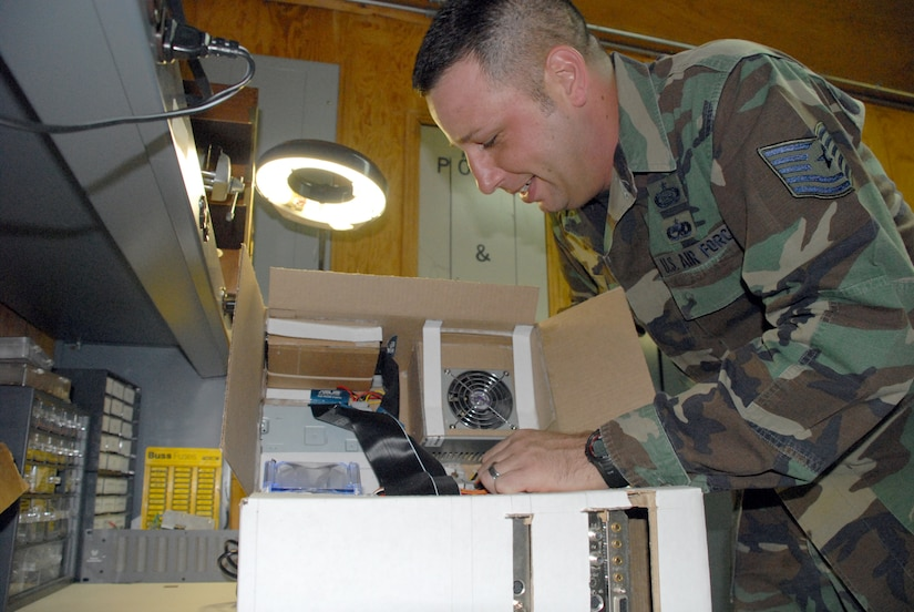 """SOTO CANO AIR BASE, Honduras -- Tech. Sgt. Robert Russell, Armed Forces Network Honduras chief engineer, makes an adjustment to his """"Frankenstein computer"""" he built from spare parts and a shipping box. The computer took about two weeks to build, since he had to wait on the glue to dry and cure after each computer component was added.  (U.S. Air Force photo/Tech. Sgt. Sonny Cohrs)"""