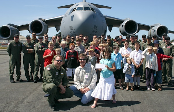 """Reserve and active-duty Airmen from the 446th and 62nd Airlift Wings taking part in Operation Deep Freeze present a check to the """"Cookie Munchers"""" organization. Each year the Airmen from McChord Air Force Base, Wash., contribute to a different organization located in their Operation Deep Freeze staging area, Christchurch, New Zealand.  (U.S. Air Force photo)"""