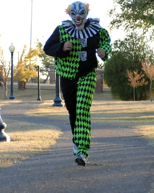CANNON AIR FORCE BASE, N.M. -- Senior Master Sgt. Patrick Fry, 27th Special Operations Services Squadron, dressed as a clown, makes his way into the last stretch of the Spooky 5K run held here Tuesday. Sergeant Fry was awarded first place for best costume.(U.S. Air Force photo by Airman 1st Class Evelyn Chavez)