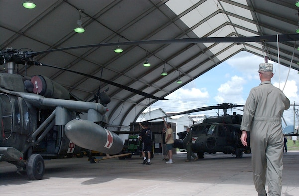 Chief Warrant Officer 4th Class Timothy Connor, a member of the 1st Battalion, 228th Aviation Regiment at Soto Cano Air Base, Honduras, guides the rotor blade of a UH-60 Blackhawk as it is moved off the flightline into a hangar. The 1-228th is taking preparations prior to the landfall of Hurricane Felix. U.S. Air Force photo by Senior Airman Shaun Emery.