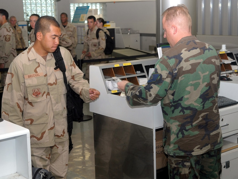 Tech. Sgt. Douglas Nall checks Airman Jonathan Bruchal's ID against the passenger manifest at Kadena Air Base, Japan, Sept. 2, 2007.  More than 240 Airmen from seven bases in Pacific Air Forces deployed from the base to Southwest Asia to support operations Iraqi Freedom and Enduring Freedom.   Sergeant Nall is with the 18th Logistics Readiness Squadron at Kadena and Airman Bruchal is with the 735th Air Mobiliity Squadron at Hickam Air Force Base, Hawaii.  U.S. Air Force photo/Maj. Dani Johnson