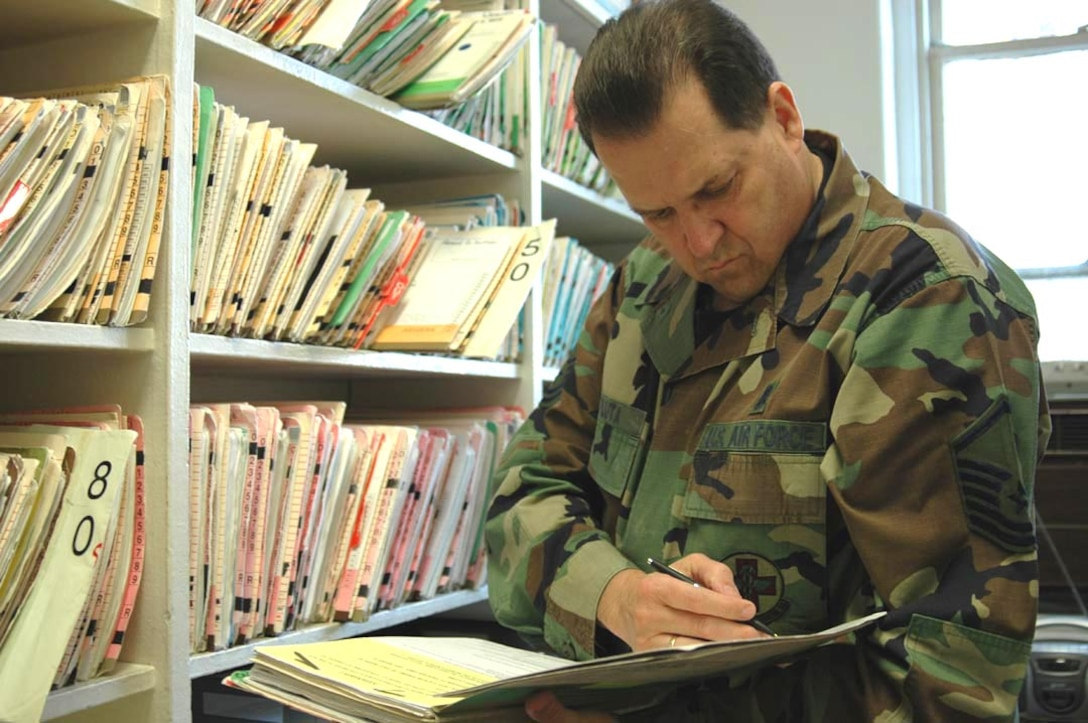 Master Sgt. Thomas Pluta, health service manager, in the record room, checks an Airman's medical record for immunization history. The record room contains over 600 individual medical records. (U.S. Air Force photo/Staff Sgt. Kevin Tomko)