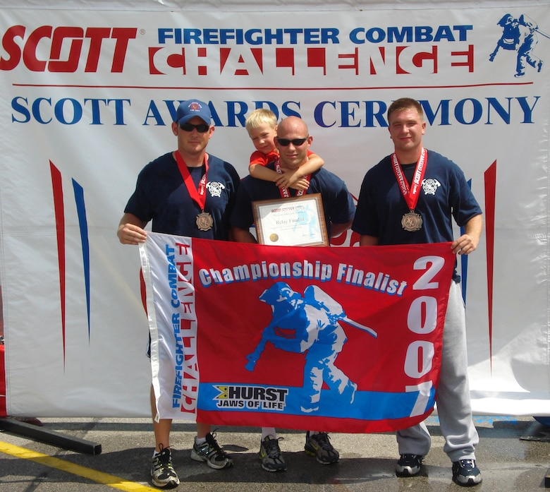 Left to right: Christopher Finkes, Staff Sgts. Cory McGee and Joshua Miller, all from the 509th Civil Engineer Squadron, and Ayden McGee, son of Sergeant McGee, display the Scott Firefighter Combat Challenge's finalist banner awarded to Sergeant McGee after he won the challenge in Omaha, Neb., Aug. 18-19. The firefighters, who comprise a three-man firefighting team from Whiteman, also represented the base the following weekend at Sioux Falls, S.D., Aug. 23-26. (Photo printed with permission of Staff Sgt. Joshua Miller)