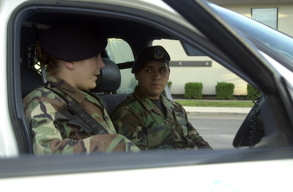 Airman Tara Port and Airman 1st Class Stephen Rivera discuss the vehicle they just pulled over Aug. 23. (U.S. Air Force photo by Airman 1st Class Stephen Musal)