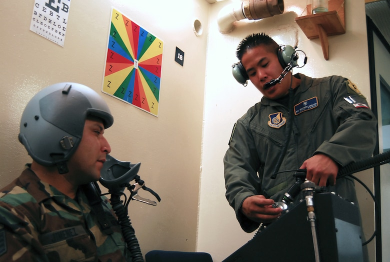 Airman 1st Class Reynato Ancheta demonstrates to Staff Sgt. Pedro Jimenez how to connect the mask breathing unit into the altitude chamber's oxygen supply Aug. 28, 2007, Kadena Air Base, Japan.  The mission of the altitude chamber is to teach military personnel who fly in aircraft, to identify, recognize and treat symptoms of hypoxia.  Airman Ancheta is an instructor for the Physiological Training Flight, 18th Aerospace Medicine Squadron.  Sergeant Jimenez is assigned to 36th Wing Public Affairs .  U.S. Air Force photo/Airman 1st Class Kelly Timney