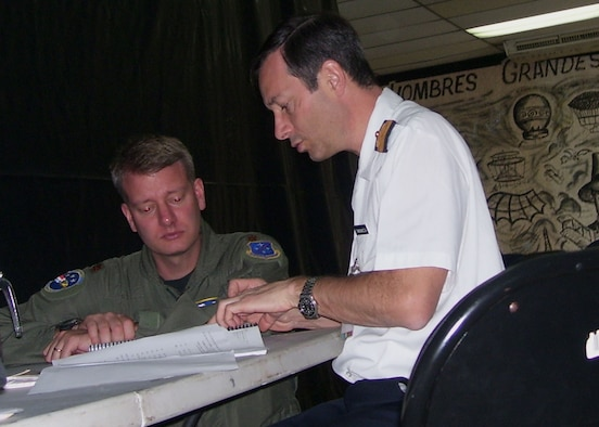 Argentinean pilot Cmdr. Fabian Magnacca (right) and United States Air Force Maj. Mark Webb, Officer in Charge Combined Forces Air Combatant Commander, discuss last minute flight communication details at Tocumen International Airport during PANAMAX 2007. Civil and military forces from 19 countries will participate in PANAMAX, a U.S. Southern Command joint and multi-national training exercise co-sponsored with the Government of Panama, in the waters off the coasts of Panama and Honduras. U.S. Navy photo by Lt. Cmdr. Bill Anderson.